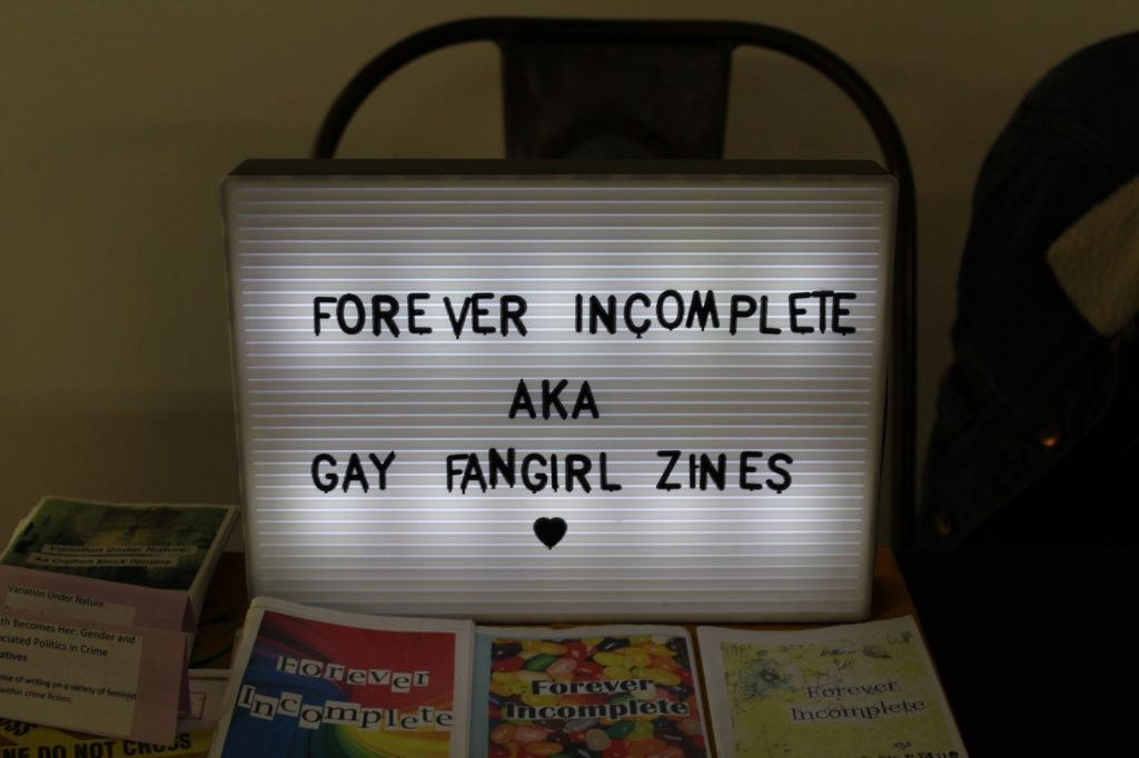 """A backlight sign with the text: """"Forever Incomplete aka gay fangirl zines"""""""