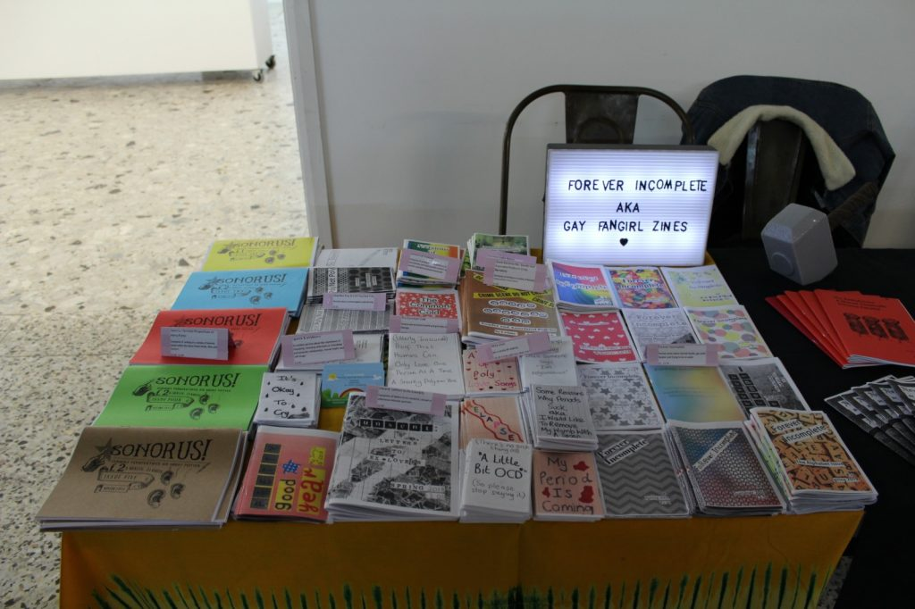 A table at a zine fest. It is covered with roughly 35 different issues of zines laid flat.